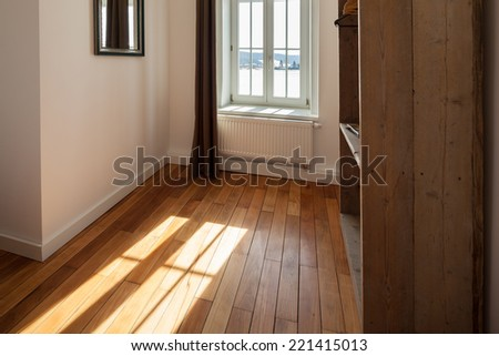 View past a shelving unit of sunlight shining onto a wooden parquet floor through a curtained window - stock photo