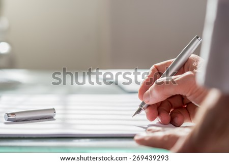 View past the arm of a colleague of a businessman writing on a document with a fountain pen, close up focus to the hand. - stock photo