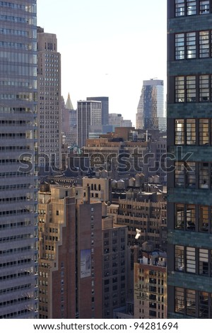 View through a gap between Manhattan skyscrapers, over New York city with a golden sparkle. - stock photo