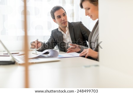 View through a partition window of two business colleagues, a stylish professional young man and woman, having a discussion sitting together going through a report and paperwork at a desk. - stock photo