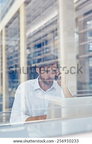 View through a window of a corporate executive working on his laptop and talking on a mobile phone - stock photo