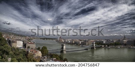 View through green trees  of the Danube river and city landmarks as Chain bridge and Parliament in Budapest in Hungary under a dramatic cloudy sky in a sunny summer day - stock photo