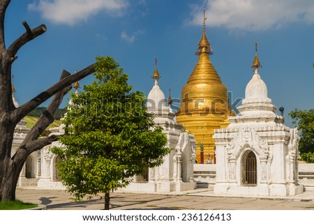 View through some white stupas to the golden Kuthodaw Pagoda in Mandalay. 729  stupas with a marble slab inscribed on both sides surround the main pagoda, such making it the largest book in the world. - stock photo