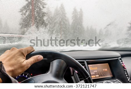 View through the cars windshield  in the winter snowy day on the road - stock photo