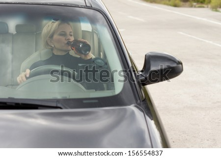 View through the front windscreen of a drunk woman driving and drinking alcohol from a bottle while travelling on the road - stock photo