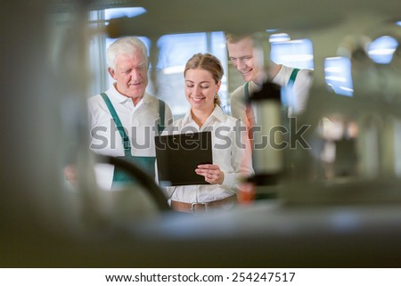 View through the machine of three workers in warehouse - stock photo
