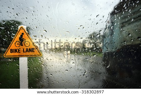 View through the wind shield of rainy day with bike lane sign,Shallow depth of field composition. - stock photo