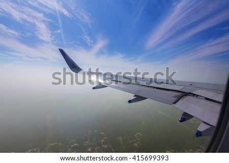 View through the window of a passenger plane flying above the city of Chennai in to the sky - stock photo