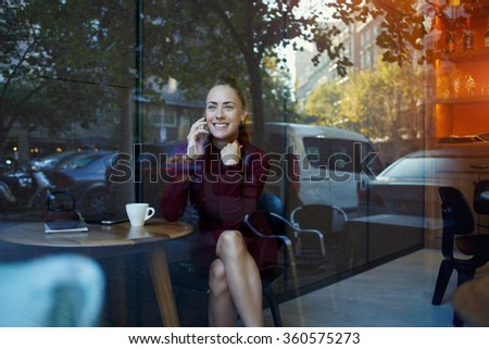View through the window of a woman with cute smile having mobile phone conversation while resting after work day in cafe, young cheerful female calling with cell telephone while sitting in coffee shop - stock photo