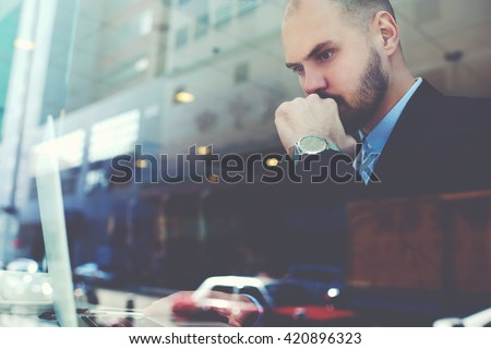 View through the window of a young man professional banker with luxury watch on hand is fulfilling an important banking operations in internet via his portable laptop computer. Double exposition - stock photo