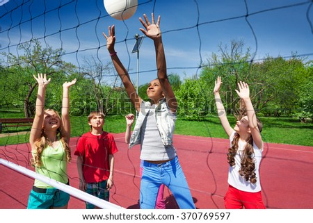 View through volleyball net of playing children - stock photo