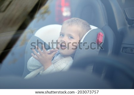 View through windshield of child siting in seat clapped hands  - stock photo