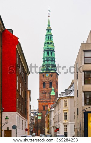 View to Former St Nicholas church in Copenhagen, Denmark in winter. The Nikolaj Contemporary Art Center is an arts center which occupies the former St Nicholas Church, a city conspicuous landmark - stock photo