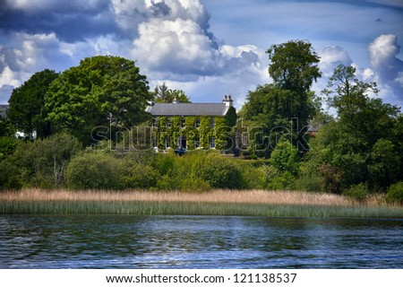 View to Irish cottage from boat river Shanon - stock photo