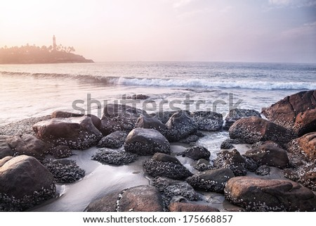 View to Lighthouse on the hill from the stones near the ocean in Kovalam, Kerala, India   - stock photo