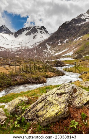 View to snow on Caucasus mountains over clear water stream near Arkhyz, Karachay-Cherkessia, Russia - stock photo