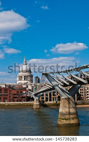 view to St. Paul's cathedral over Millennium bridge in London, United Kingdom (blue sky clouds) - stock photo