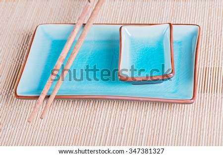 View to sushi setting: bamboo mat, dish and chopsticks - stock photo