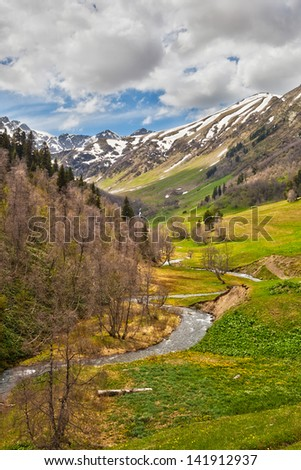 View to the foothills of the Caucasus mountains over flowers and stream near Arkhyz, Karachay-Cherkessia, Russia - stock photo
