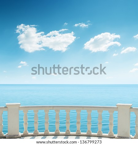 view to the sea from a balcony under cloudy sky - stock photo