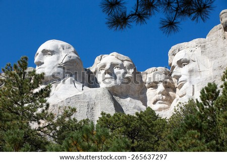 View up to the four Presidents faces - Lincoln, Roosevelt, Jefferson and Washington - sculpted into the granite rock on Mount Rushmore, South Dakota, USA framed by green pine trees against blue sky - stock photo