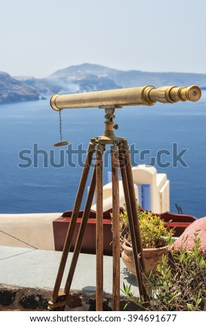 View with a telescope from a restaurant terrace in Oia, Santorini island in Greece. - stock photo