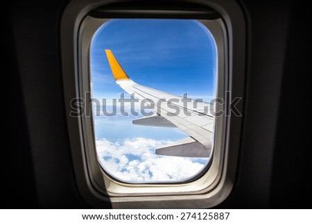 viewpoint Wing of windows airplane flying above the clouds in the sky - stock photo
