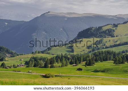 Views of Alpe di Siusi meadows and surrounding Dolomite mountain ranges as seen from hotel Panorama, the largest high altitude alpine plateau in Europe and major tourist attraction, South Tyrol, Italy - stock photo