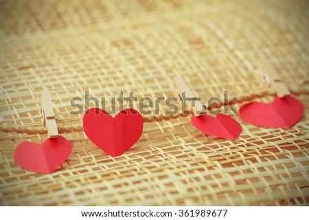 Vignette Style, Series of Valentines Card. Four Red heart paper cut with clothes pin on wooden weaving background, in very shallow focus. Image of Valentines day. - stock photo