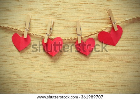 Vignette Style, Series of Valentines Card. Four Red heart paper cut with clothes pin on wooden background, in very shallow focus. Image of Valentines day. - stock photo