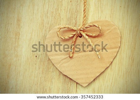 Vignette Style, Series of Valentines Card, Heart Shape Blank Cardboard with Flax Cord hanging over wood background. Photoshop Vintage Effect. - stock photo