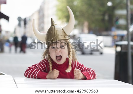 viking blond girl in red shirt in preschool age sitting at table, screaming and waiting for food in cafe outdoors, wearing costume hat with horns - stock photo