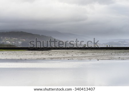 VILABOA, SPAIN - FEBRUARY 15, 2015: A group of athletes, practicing running on a breakwater in a cove of the Ria de Vigo in Galicia. - stock photo