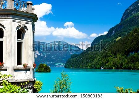 Villa on a scenic turquoise mountain lake - stock photo