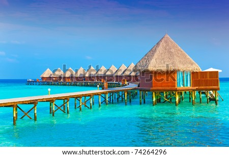 Villa on piles on water at the time sunset. - stock photo