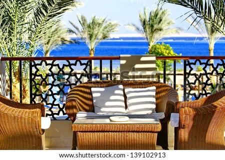 Villa terrace with wicker furniture and sea view - stock photo