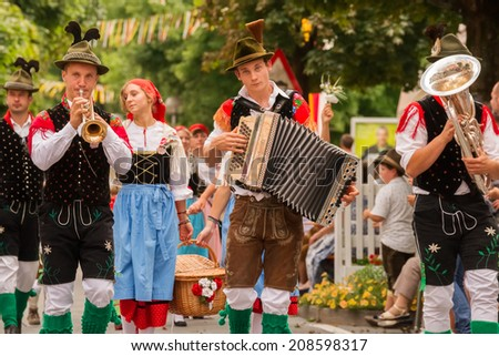 VILLACH, AUSTRIA - AUGUST 2: Young traditional musicians at the procession of 'Villacher Kirchtag', the largest traditional folk festival in Austria, August 2, 2014 in Villach, Austria. - stock photo