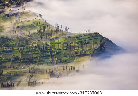 Village and Cliff at Bromo Volcano in Tengger Semeru national park, Java, Indonesia - stock photo