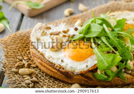 Village bread, fried eggs, roasted nuts and small salad on top, simple but delicious. - stock photo