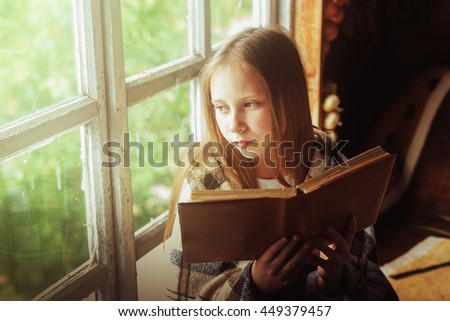 Village girl with a book by the window. - stock photo