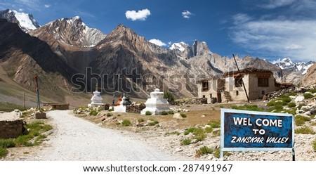 Village in Suru valley and signpost Welcome to Zanskar valley, road from Kargil to Padum, Zanskar valley, Ladakh, Jammu and Kashmir, India - stock photo