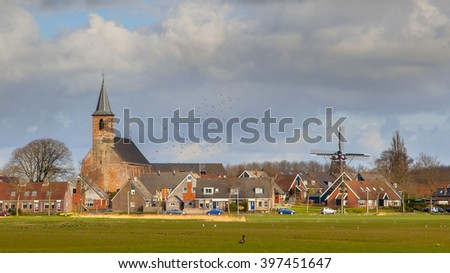 Village of Burdaard with church an historic windmill on Frisian countryside. Just North of Leeuwarden, Friesland. - stock photo