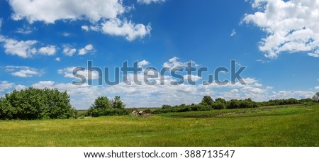 Village panorama spring - spacious green meadow, blue sky with clouds, With copy text. Panorama Ukrainian village - meadow and houses in the distance. - stock photo