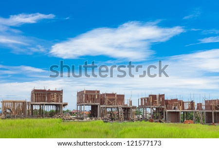 Villas under construction in Bali. Houses are being built in the middle of farming rice fields. - stock photo