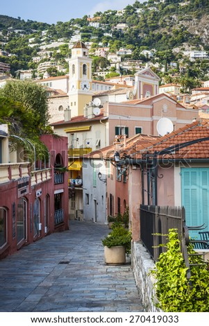 VILLEFRANCHE-SUR-MER, FRANCE - OCTOBER 4, 2014: Cobblestone street with colourful buildings leads to the heart of old town and Eglise Saint-Michel (Saint Michael's Church). - stock photo