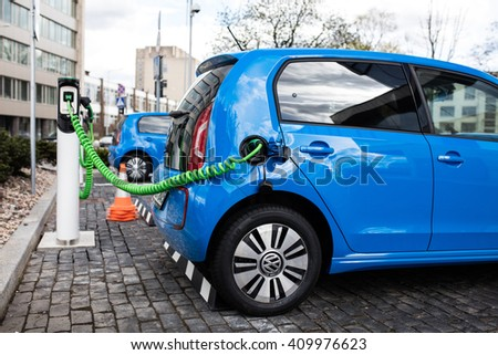 Vilnius, Lithuania - April 23, 2016: Power supply for electric car charging. Electric car charging station. Close up of the power supply plugged into an electric car being charged. - stock photo