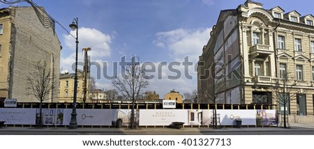 VILNIUS, LITHUANIA - MARCH 27 2016: Fragment of the capital of Lithuania - Gediminas Avenue. Behind a fence a ditch for the new modern house. Solar spring morning. Construction is done by Keista firm - stock photo