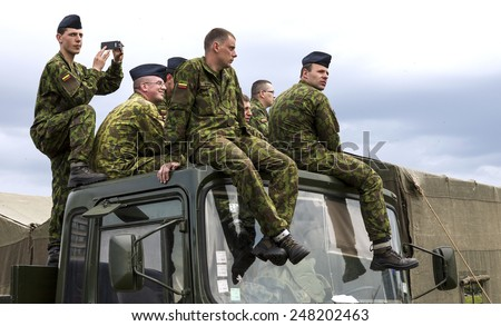 VILNIUS, LITHUANIA - MAY 17, 2014: Lithuanian army soldiers sitting on the top of military truck during Public and Military Day Festival in Vilnius, Lithuania - stock photo