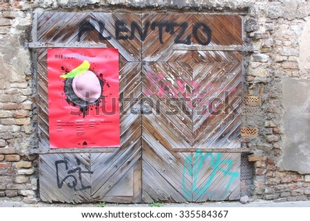 VILNIUS, LITHUANIA  - October 4. Grungy garage doors with graffiti and a poster on October 4, 2015 in Uzupio (Uzupis), a suburb in the Old Town of Vilnius. - stock photo