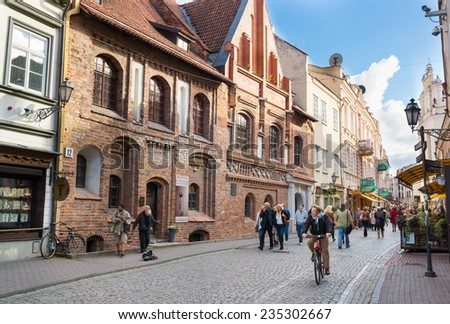 VILNIUS, LITHUANIA - SEPTEMBER 26: Tourists visit one of the most popular Pilies street of the old town on September 26, 2014 in Vilnius, Lithuania. - stock photo
